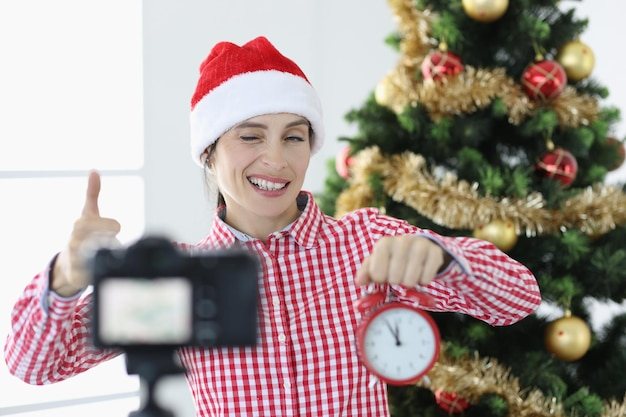 La giovane blogger con il cappello di babbo natale tiene la sveglia e strizza l'occhio alla telecamera di capodanno