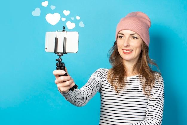 La giovane donna blogger scatta foto di se stesso al telefono su una parete blu. storia concettuale, vlog, selfie, blog.