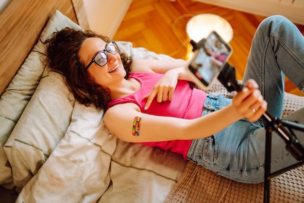 Blogger di giovane donna che parla con i follower, live streaming sul vaccino per il covid-19.