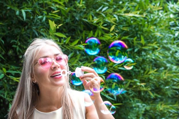 Giovane donna soffia bolle di sapone in strada