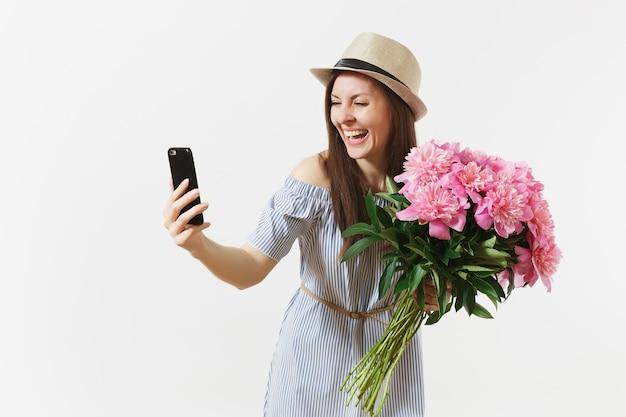 Giovane donna in abito blu, cappello che tiene il mazzo di bellissimi fiori di peonie rosa, facendo selfie sul telefono cellulare isolato su sfondo bianco. san valentino, concetto di vacanza per la giornata internazionale della donna.
