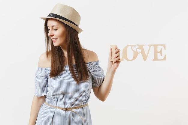 Giovane donna in abito blu, cappello che tiene in legno parola amore isolato su sfondo bianco. san valentino, festa della giornata internazionale della donna. persone, emozioni sincere, concetto di stile di vita. zona pubblicità.