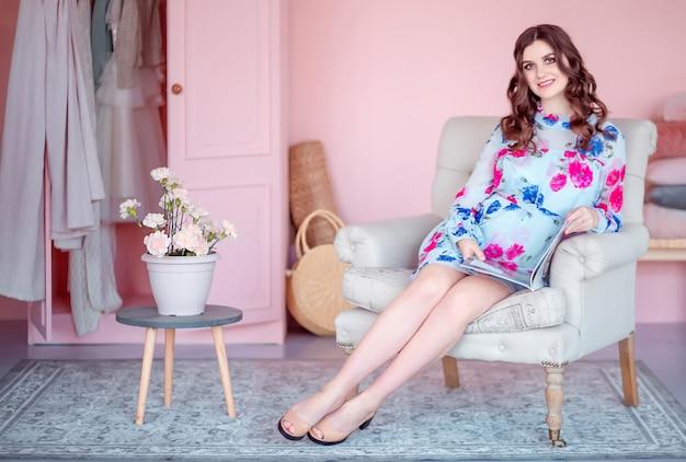 La giovane donna in vestito blu si siede in poltrona e legge la rivista