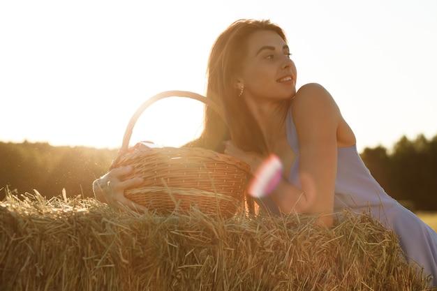 Una giovane donna in abito blu con un mazzo di margherite è seduta su un pagliaio in un campo falciato