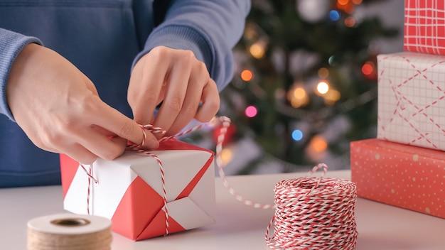 Una giovane donna in blu sta avvolgendo, confezionando un regalo di natale per bambini con un bellissimo involucro rosso e bianco con luce scintillante, stile di vita.