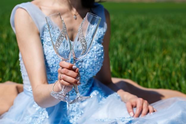 La giovane donna in un vestito lungo blu tiene un vetro nelle sue mani