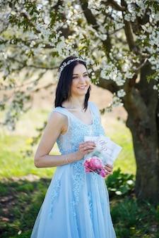 La giovane donna in un vestito lungo blu tiene un aliante di nozze nelle sue mani