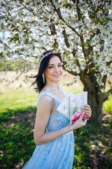 La giovane donna in un vestito lungo blu tiene un taccuino di nozze nelle sue mani