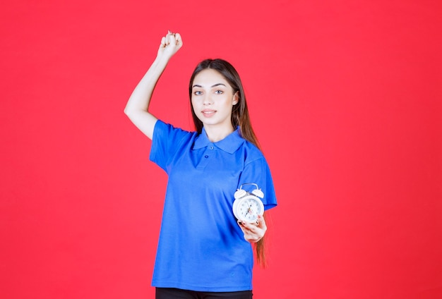 Giovane donna in camicia blu che tiene una sveglia e mostra il segno positivo della mano