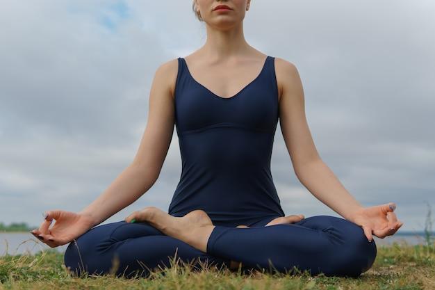 Giovane donna in abiti sportivi blu seduto in posa yoga, cielo nuvoloso e lago sullo sfondo.