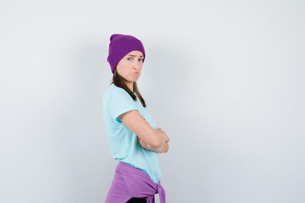 Giovane donna in maglietta blu, berretto viola in piedi con le braccia incrociate, guardando sopra la spalla e guardando sconvolto, vista frontale.