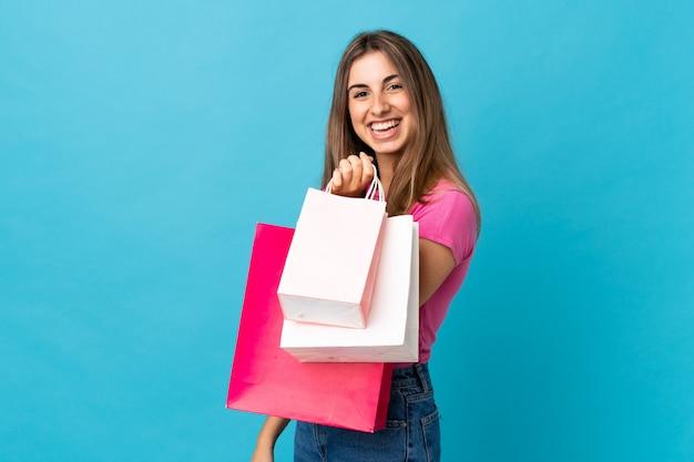 Giovane donna sopra i sacchetti della spesa e sorridere blu della tenuta della parete