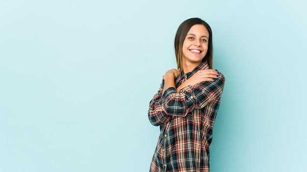 Giovane donna sugli abbracci blu della parete, sorridente spensierato e felice.