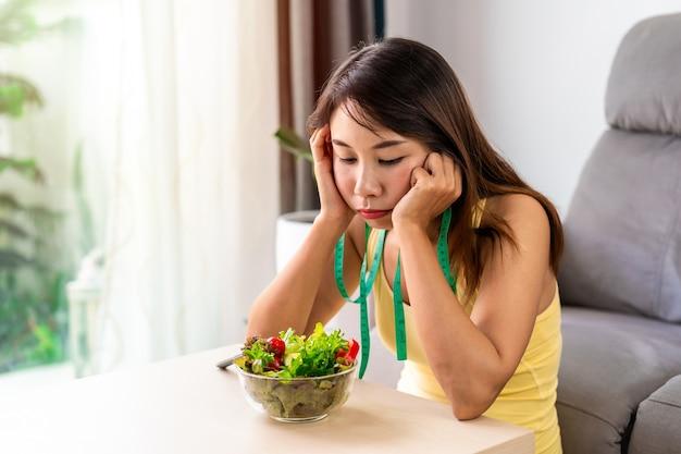 Giovane donna noiosa mentre mangia verdura fresca a casa e stile di vita mangiare sano e concetto di dieta