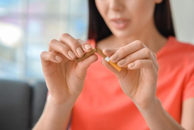 Giovane donna che rompe la sigaretta a casa. concetto di rifiuto dalla cattiva abitudine