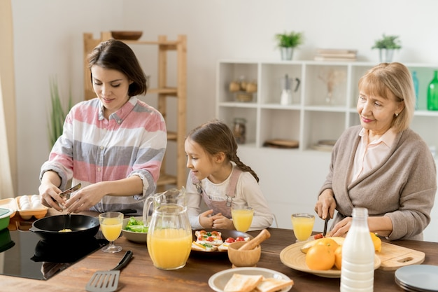 Giovane donna che rompe uovo sopra la padella calda durante la cottura della colazione per sua figlia e sua madre
