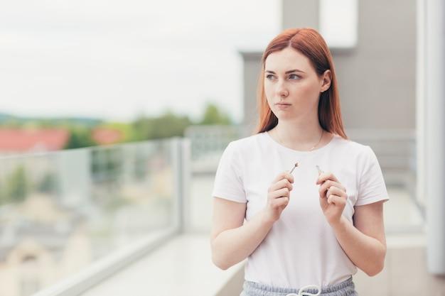 Una giovane donna rompe una sigaretta come segno che ha smesso di fumare