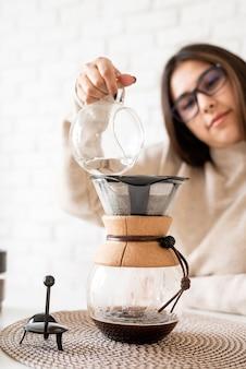 Giovane donna che prepara il caffè nella macchina per il caffè in piedi al tavolo bianco con varie cose per la preparazione alternativa del caffè, versando acqua calda nel filtro