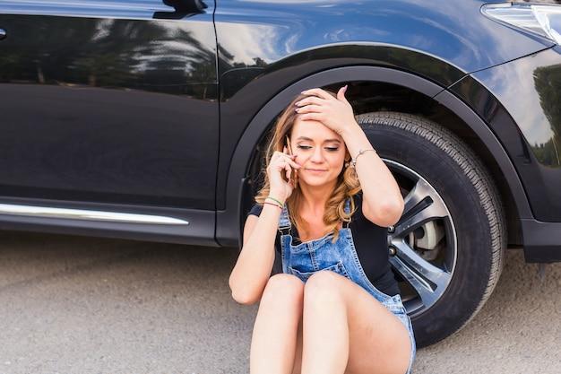 Giovane donna e automobile rotta che chiedono aiuto sul telefono cellulare.
