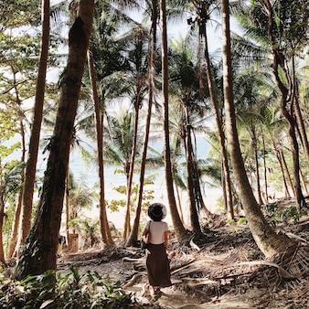 Una giovane donna in gonna marrone, camicia bianca e cappello di paglia nero in piedi nella giungla con molte palme esotiche