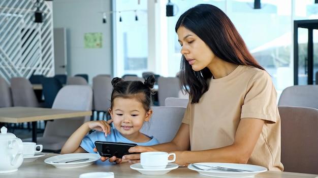 Giovane donna bruna e bambino piccolo guardano video su gadget