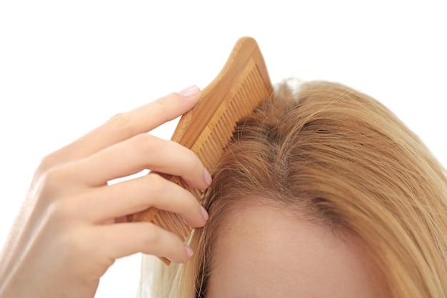 Giovane donna che spazzola i capelli, primo piano