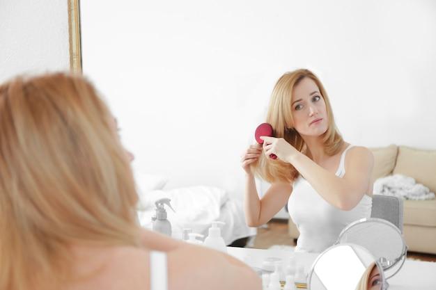 Giovane donna che spazzola i capelli davanti allo specchio a casa