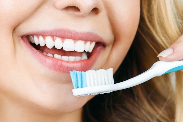 Giovane donna che pulisce i suoi denti
