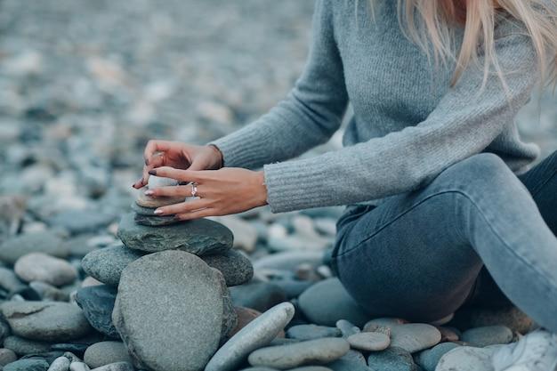 La giovane donna costruisce piramide di pile di pietra sulla spiaggia di ciottoli