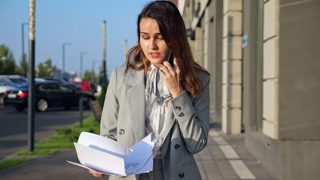 La giovane donna in giacca e cravatta sta parlando emotivamente al telefono e guardando i documenti camminando per strada