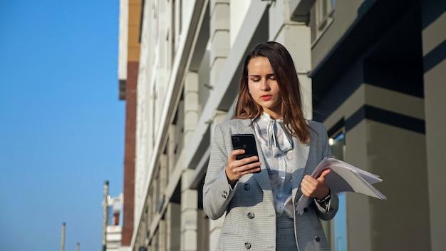 Giovane donna in giacca e cravatta con un telefono e documenti che camminano per strada.