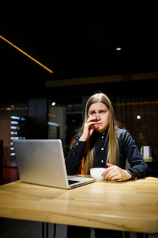 La giovane donna d'affari è seduta al computer e ha mal di testa per una lunga giornata di lavoro