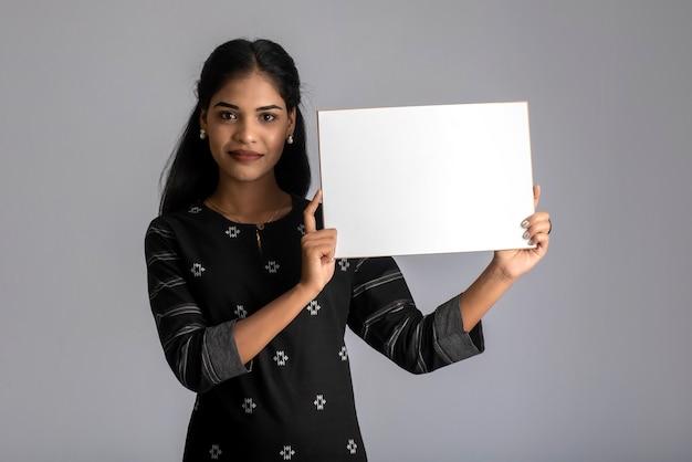Una giovane donna o imprenditrice con un cartello in mano su uno sfondo grigio.