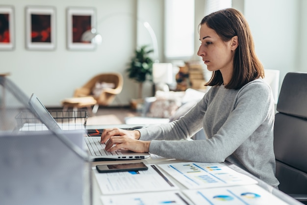 Giovane donna impegnata a lavorare in ufficio a casa.