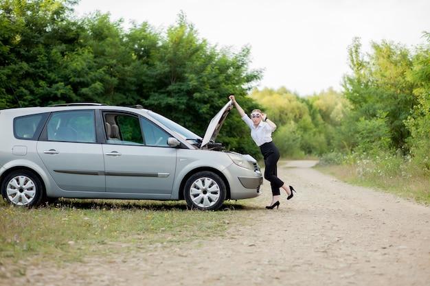 Giovane donna sul ciglio della strada dopo che la sua auto si è rotta. ha aperto il cofano per vedere i danni.