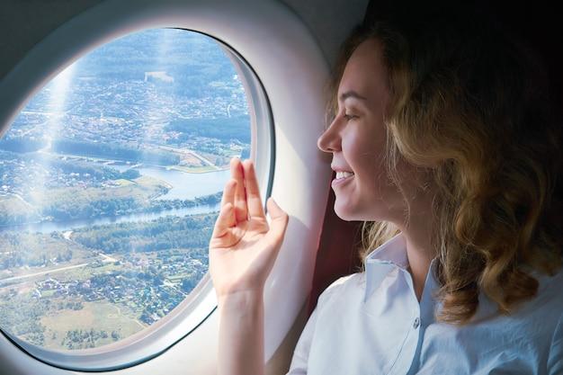 La giovane donna nella cabina di un aereo di atterraggio guarda attraverso l'oblò il terreno sottostante