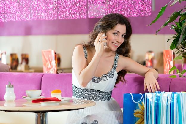 Giovane donna in un bar o in una gelateria che mangia una torta e usa il suo telefono, forse è single o sta aspettando qualcuno