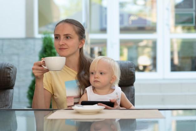 La giovane donna nella caffetteria con il bambino in braccio beve il caffè e guarda il telefono. mamma moderna di affari.