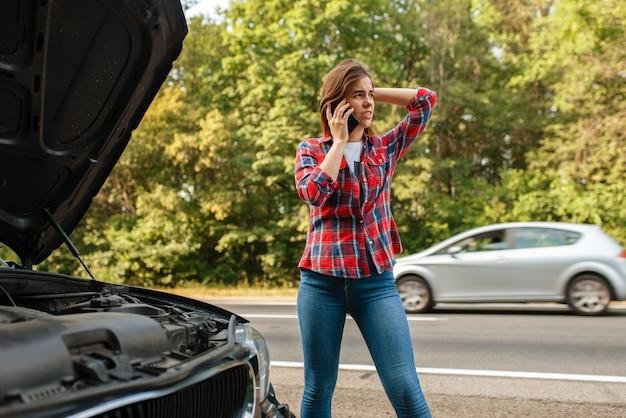 Giovane donna che chiama un carro attrezzi su strada, guasto auto. automobile rotta o incidente di emergenza con il veicolo, problemi con il motore sull'autostrada