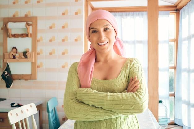 Una giovane donna sopravvissuta al cancro che indossa una sciarpa rosa, sorride con le braccia incrociate e guarda la telecamera