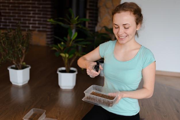 Giovane donna che si prende cura di microgreens in un piccolo appartamento. una donna dai capelli rossi che innaffia i microgreens a casa
