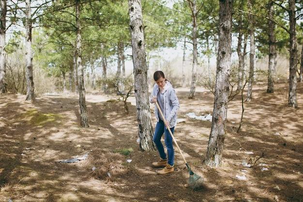 Giovane donna in abiti casual che pulisce la spazzatura usando il rastrello per la raccolta dei rifiuti nel parco o nella foresta disseminati. problema di inquinamento ambientale