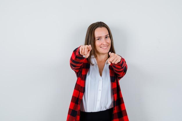 Giovane donna in abiti casual che punta alla telecamera e sembra allegra, vista frontale.