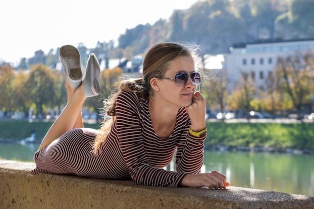 Giovane donna in un abito casual e occhiali da sole di riposo all'aperto in una calda giornata d'autunno.