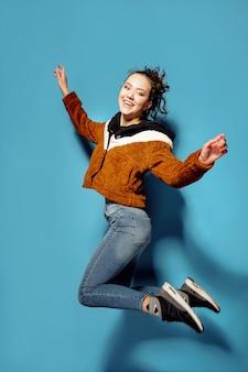 Giovane donna nel salto casuale in aria sopra fondo blu