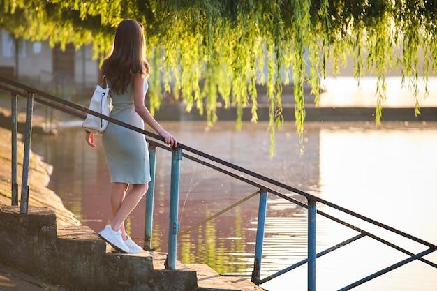 Giovane donna in abito casual rilassante sul lato del lago in una calda serata. vacanze estive e concetto di viaggio.
