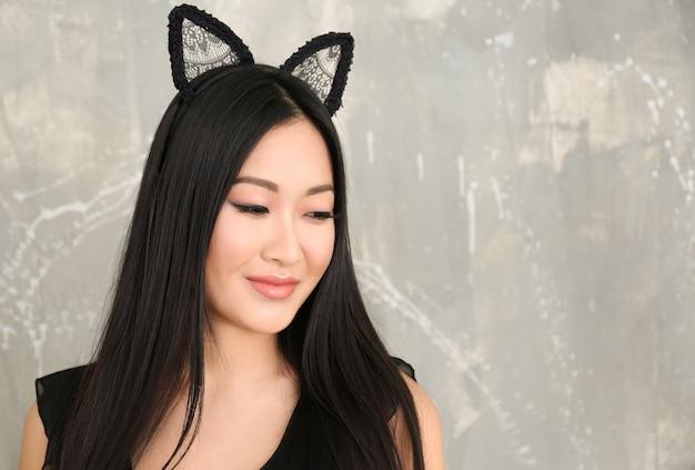 Giovane donna in orecchie di gatto su sfondo colorato