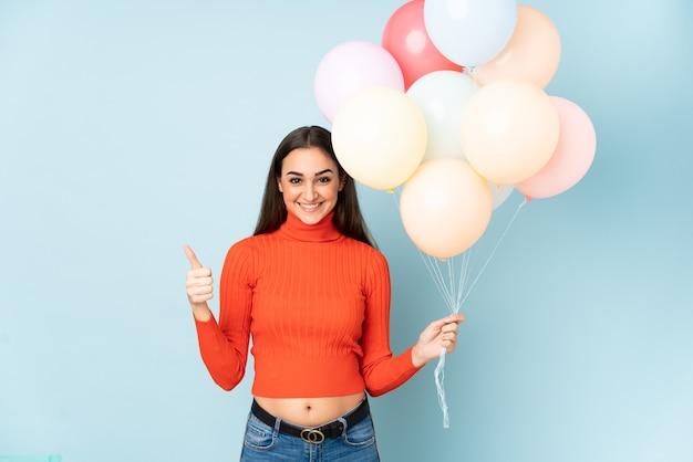 Giovane donna che cattura molti palloncini isolati su blu dando un pollice in alto gesto