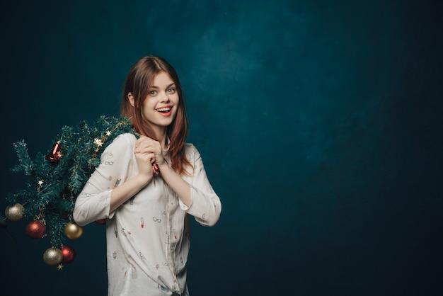 Giovane donna che celebra il natale e il nuovo anno con l'albero di natale