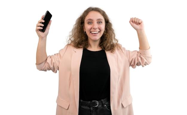 Giovane donna che celebra una vittoria con il suo smartphone in mano